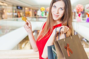 Fashion successful woman holding credit card and bags, shopping mall